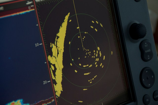 A radar screen aboard the auxiliary race committee boat shows the blips of competitors circling before the race begins. The shoreline is on the left. (Credit: Paul Squire)