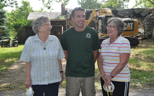 Michael Bredemeyer (center) with his grandmother, Jeanne, (left) and mother, Beverly, standing in front of the demolition.  (Credit: Cyndi Murray)