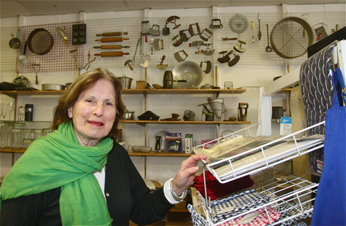 Arlene Marvin in her store Cookery Dock, which she has owned for 44 year at 132 Main Street in Greenport. Her customers tell her their favorite thing about the place are the antique cooking equipment she has on display on the side wall. (Credit: Barbaraellen Koch)