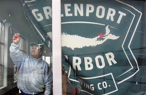 Greenport Harbor Brewing Company worker Enfivfo Cruz cleans windows that line the former Lucas Ford showroom on Main Road in Peconic. The building and an adjoining one are being renovated to house a restaurant and the beer company's second brewing facility. (Credit: Barbaraellen Koch)