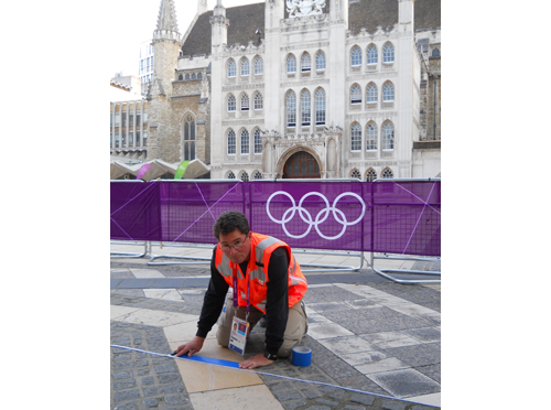 David Katz taping down a blue line, marking the marathon route for the 2012 London Olympic Games. (Credit: courtesy)