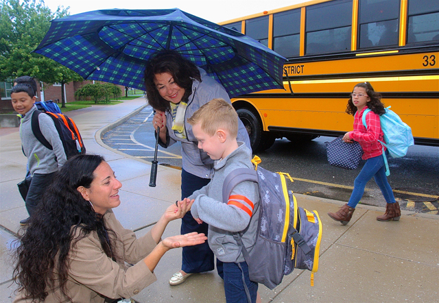 Teacher assistants Jaalyn Jimenez (left) and Pam Farmer greet kindergartener Mason Despres as he arrived.