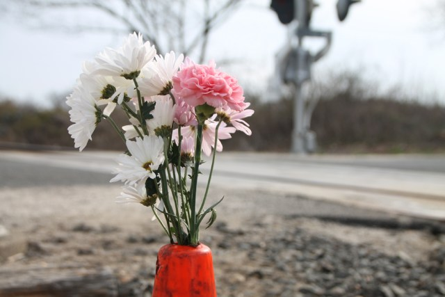 A few flowers stand in a traffic cone set up as an impromptu memorial to Frank McBride at the scene of Tuesday's accident in Mattituck. (Credit: Paul Squire)