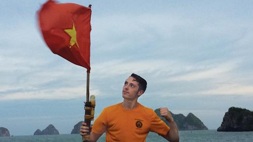 Ian Husak with the Vietnamese flag on a fishing boat in Ha Long Bay. (Credit: Ian Husak courtesy photos)