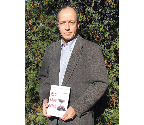 CARRIE MILLER PHOTO | Joseph Finora with his first novel, which takes place in Wine Country.