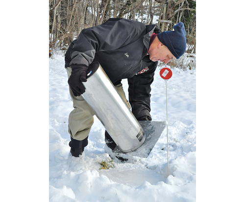 TIM KELLY PHOTO  |  Lenny Llewellyn demonstrates snow-measuring equipment at his Mattituck home.