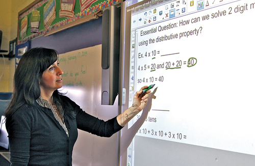 JENNIFER GUSTAVSON PHOTO  |  Our Lady of Mercy teacher Marianne Wachtel works at her classroom's Smartboard.