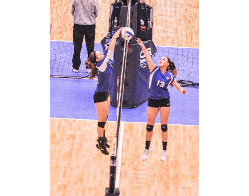 JIM ELLIS PHOTO | Mattituck's senior setter, Laurel Bertolas, right, has company at the net during one of her team's games against Millbrook in the NYSPHSAA Championships at Glens Falls Civic Center.