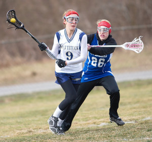 GARRET MEADE PHOTO | Katie Hoeg, who had 6 goals and 3 assists in Mattituck/Greenport/Southold's season-opening win, trying to maneuver around Riverhead's Isabella LoPiccolo.