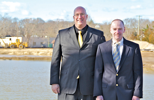 CARRIE MILLER PHOTO | Bishop McGann-Mercy High School principal Carl Semmler (left) and Shawn Leonard, a Mercy graduate and architect for the school's planned pond remediation project, at the foot of the pond on school grounds last week.