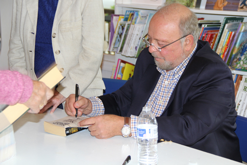 "CARRIE MILLER PHOTO | Nelson DeMille signs a copy of his new book ""The Quest"" at BookHampton in Mattituck Saturday."