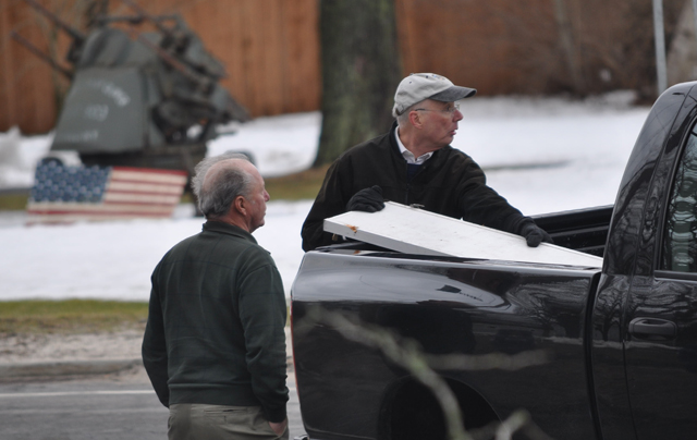 Pastor Jef Gamblee of First Universalist Church in Southold, with church member Peter Young of Southold, load the church sign into a pickup truck before driving it to a service at  Custer Institute. (Credit: Grant Parpan)