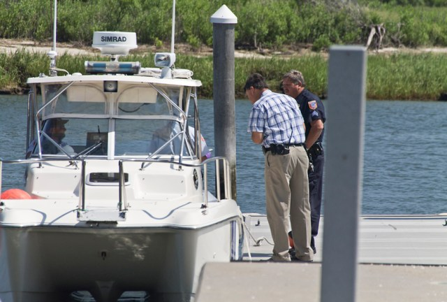 Southold Town police sergeants confer with town marine unit officers after they arrived in Mattituck about noon Monday with the crash victim's body on board. (Credit: Paul Squire)