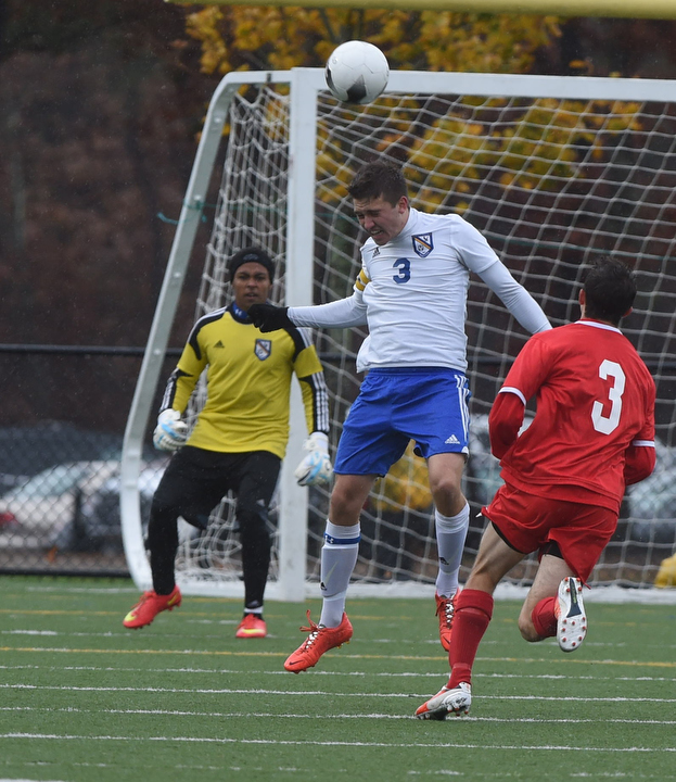Kevin Williams on defense for Mattituck heads a ball away from his goal. (Credit: Robert O'Rourk)