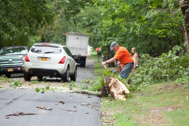 John Fudjinski clears a fallen tree on New Suffolk Avenue. (Credit: Katharine Schroeder)