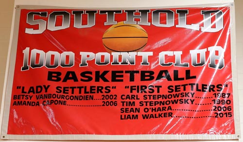 A banner hanging in the Southold High School gym lists four males who have scored 1,000 career points for the First Settlers. (Credit: Garret Meade, file)