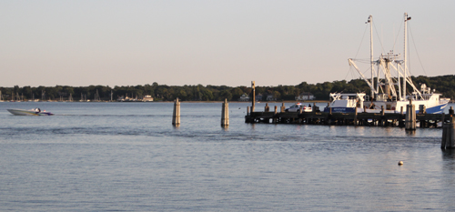 Passegers of this cigarette boat (left) were ejected into Greenport Harbor on Monday. (Credit: Jen Nuzzo)