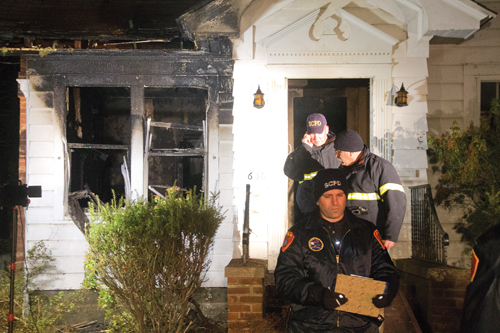 Investigators leave the home of Karen Pollack March 5 — the night her husband, Jack, was killed in a house fire. Nearly a year later, she's still working to get back into the house. (Credit: Paul Squire, file)