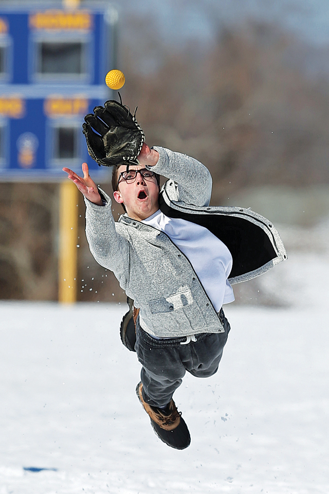 Jonathan Dwyer dives to catch the ball on a snowy field. Mattituck HS had its first outdoor practice of the season in the snow on March 9th 2015.Daniel De Mato
