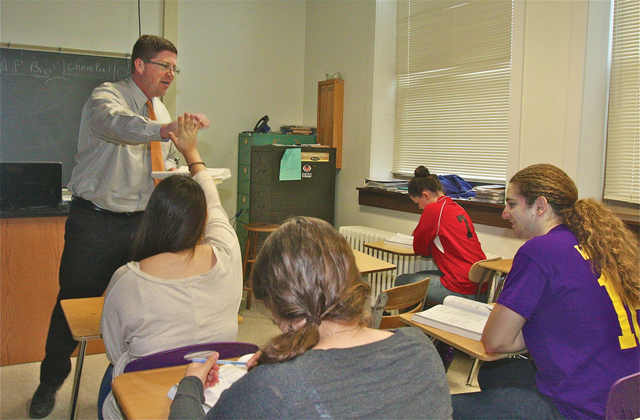 Greenport High School AP biology teacher Christopher Buckley gives student Sophia Albizures a high-five after she correctly answers a question about Mendelian genetics. (Credit: Barbaraellen Koch)