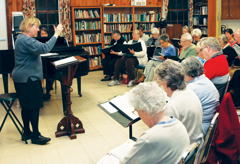 Lois Ross, left, leads the choir at a 2011 practice session of North Fork Chorale. (Credit: file photo)