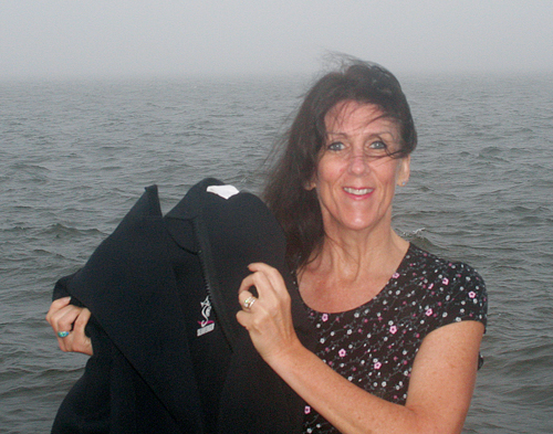 Joan Archard of Patchogue holds up her wetsuit Tuesday near Great South Bay, where she's been practicing for this weekend's swim from Greenport to Shelter Island (and maybe back). (Credit: Courtesy photo)
