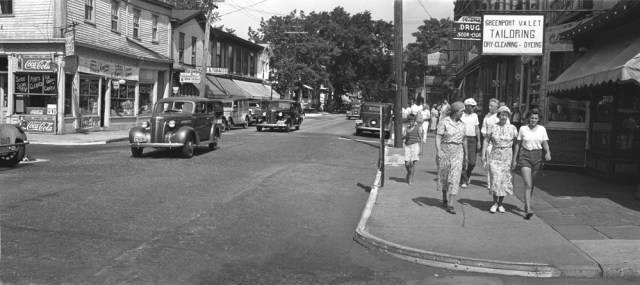 A 1950s photo of Greenport's Main Street. To the left of the photo in the street is a raised storm drain, originally installed to prevent injury to horses from stepping in the drains.