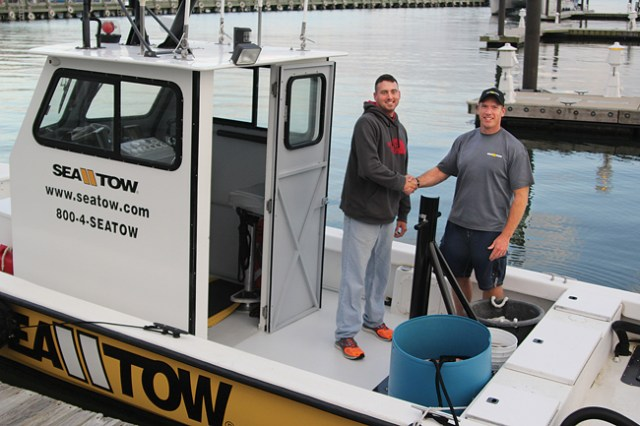 Patrick O'Halloran (left) and Garrett Moore met for the first time Tuesday evening in the Mitchell Park marina, hours after a joint effort to rescue six boaters and bring an out-of-control cigarette boat to a halt in the waters of Greenport Harbor. (Credit: Jen Nuzzo)