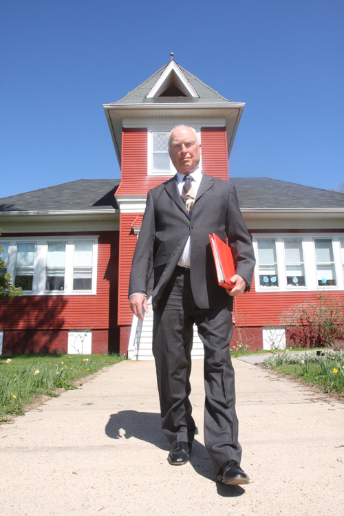New Suffolk school board president Tony Dill in front of the elementary school. The incumbent is running unopposed this year. (Credit: Barbaraellen Koch)