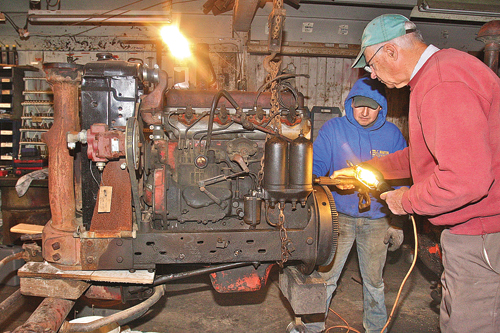 BARBARAELLEN KOCH PHOTO | Farmer Tom Wickham (right) works with equipment operator Gerardo Reyes repairing the engine of a 1947 Farmall tractor. It was the first new tractor that his family bought for the farm at the end of WWII.