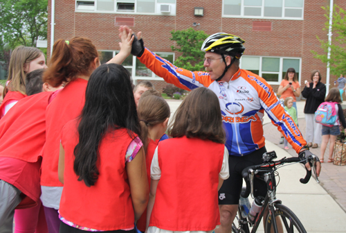 Fourth-grade teacher Skip Munisteri hands out high-fives as he reaches the school Friday morning. (Credit: Carrie Miller)