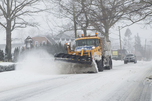 KATHARINE SCHROEDER PHOTO | A snow plow clears the road near Mattituck.