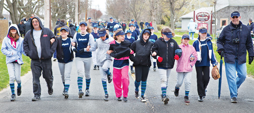 An Oysterponds team marches up Peconic Lane in Peconic with other North Fork Little League players and coaches in Saturday's opening day parade. The march proceeded to Tasker Park for games and entertainment.