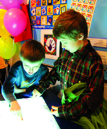 First-grader Quincy Greene (left) and his brother Hudson, a third-grader, draw on a light table at Southold Elementary School's first-ever Art/Science/Technology fair on March 24.