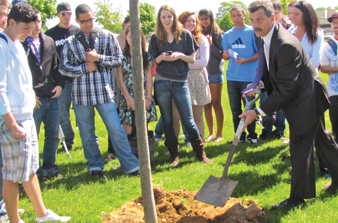 Greenport High School seniors and Superintendent Mike Comanda bury a time capsule Friday under a sapling donated to the class by the Village Board and tree committee.