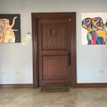 GW Art complementing a vintage door with vibrance at a lovely home.