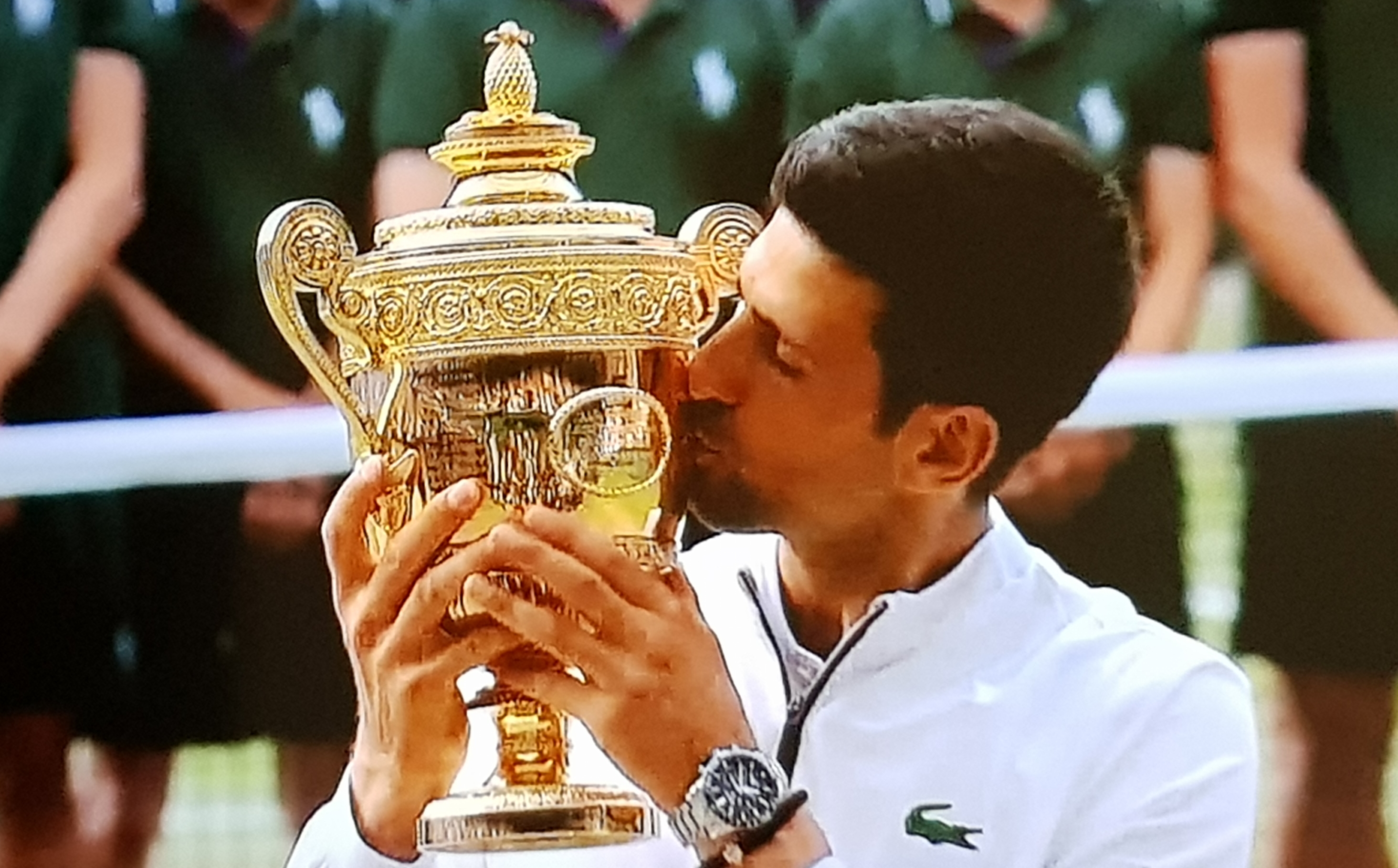 World no. 1, Novak Djokovic gives his Wimbledon Trophy some love after defeating Roger Federer last Saturday.
