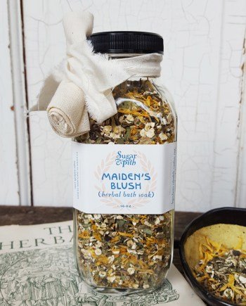 Sugar and Pith Maiden's Blush herbal soak for sensitve skin, square 16 oz bottle of herbs set on a book with a bowl of loose herbs next to it