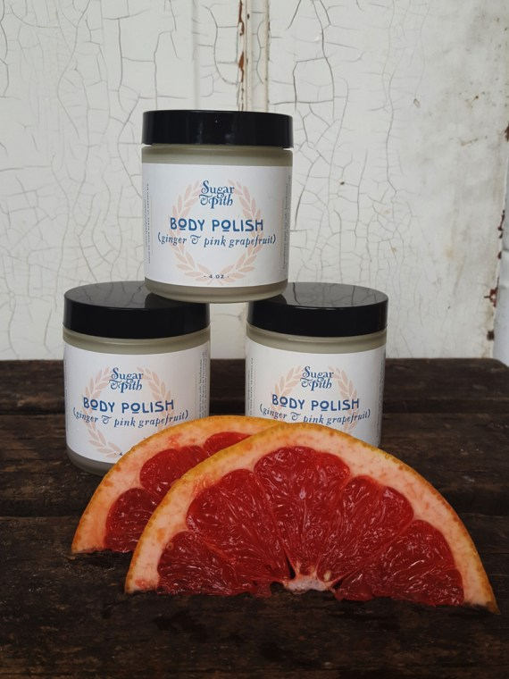 Sugar and Pith Grapefruit and ginger body polish, 3 stacked jars of body polish with two pink grapefruit wedges in front