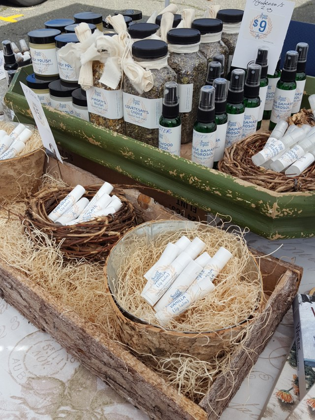 Sugar and Pith lip balm, hydrosols, and bath herbs displayed in nests and on a rustic tray