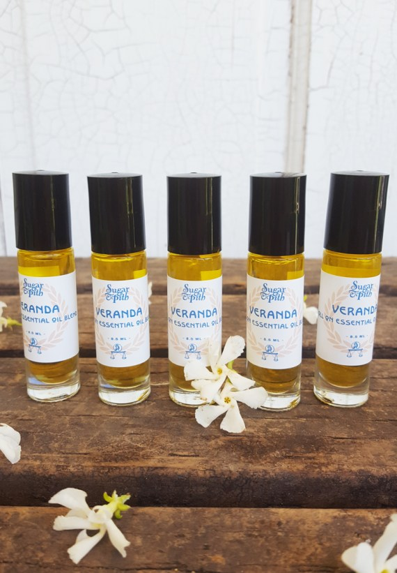 Sugar and Pith, Roll On Veranda, five roll on bottles of Veranda essential oils lined up in a row on a rustic wood table with white jasmine flowers scattered around them.