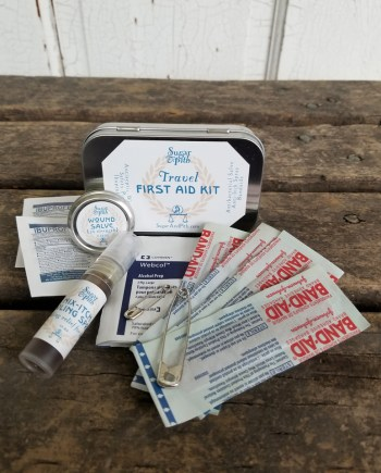 Sugar and Pith, Travel First Aid kit with contents laid out on a rustic wood table, band aids, wound salve, Nix-Itch spray