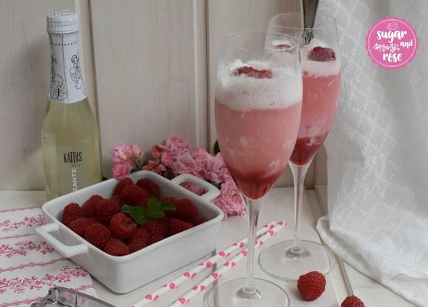 Zwei Sektgläser mit schäumendem Roseneis-Float, eine kleine Kattus-Sektflasche dahinter, davor eine weiße, quadratische Keramikschale mit Himbeeren, ein rosa geblümtes Geschirrtuch und zwei Papierstrohhalme mit rosa Herzerl drauf
