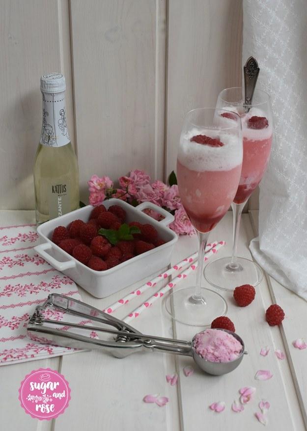 Zwei Sektgläser mit schäumendem Roseneis-Float, eine kleine Sektflasche dahinter, davor eine weiße, quadratische Keramikschale mit Himbeeren und ein Eisportioniere mit Roseneis