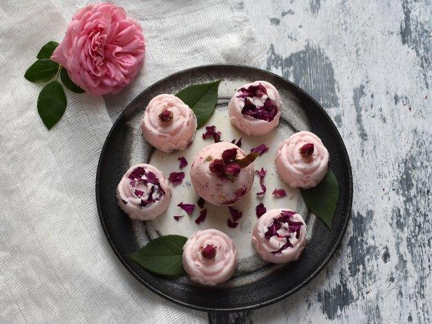 Rosa Badepralinen auf einem grauen Steingutteller, davon sechs Stück in Rosenform, eine als Badebomben-Kugel, alle dekoriert mit dunkelroten getrockneten Rosen