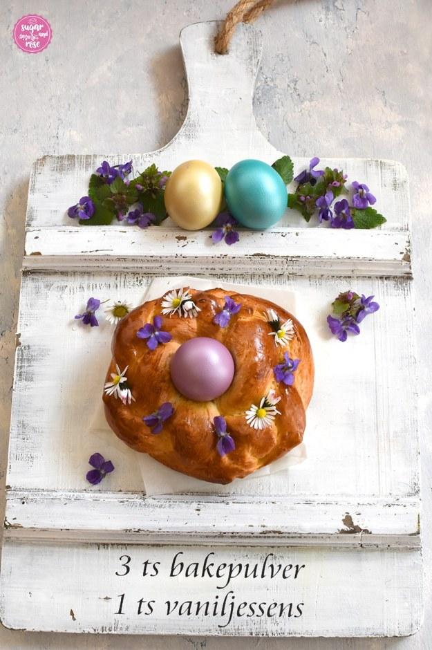 Osterkranzerl mit lila Osterei auf weißer Holzplatte