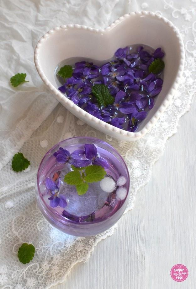 Veilchenwasser in Glas und Schale mit Veilchenblüten
