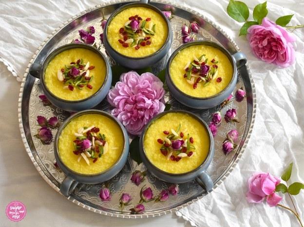 Safran-Reispudding mit Rosenwasser in Keramikschalen mit rosa Rosen