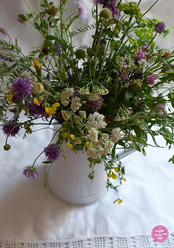 Wiesenblumenstrauß mit gelbem Hornklee, violetten Flockenblumen, rotem Hornklee und fliederfarbenen Acker-Weitwenblumen und weißer Schafgarbe in einer weißen Vintagekanne mit Henkel auf einem alten weißen Handtuch mit gehäckeltem weißem Rand