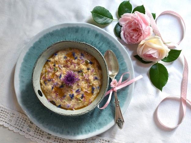 Sommer-Porridge mit bunten Wiesenblumen dekoriert: mit Kornblumen, Löwenzahn und Rotklee: Porridge in einer türkisen Schale mit türkis-weiß marmoriertem Unterteller, einem alten Silberlöffel mit rosa Mascherl, daneben porzellanrosafarbene Rosenblüte und ein rosa gepunktetes Band